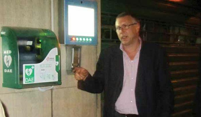 Ugo Rizzi accanto a un defibrillatore a muro